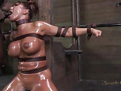 Milf Ava is tied in leather belts and her sexy body has been oiled up. She patiently awaits down on her knees for something to happen when the executor comes at her and pays this bitch some attention. He grabs her by the hair and begins to mouth fuck her deep, reminding Ava where's her place